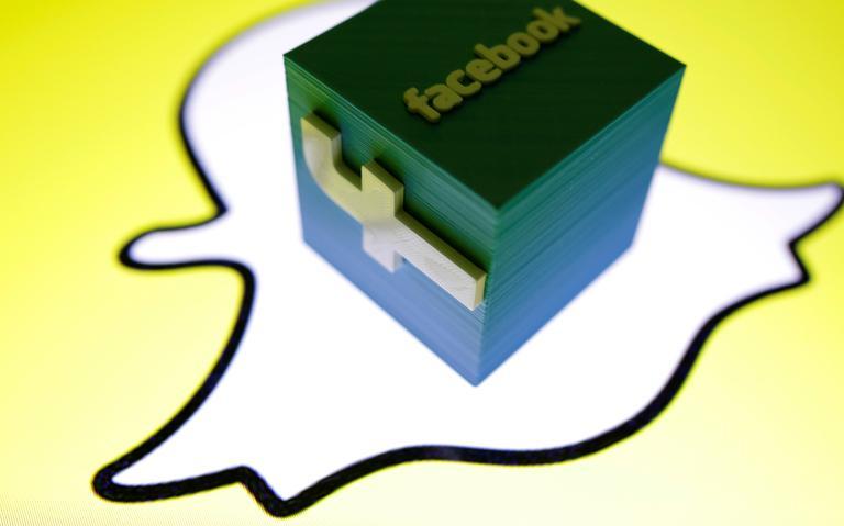 Um logotipo imprimido em 3D do Facebook sobre o logo do Snapchat. As empresas são concorrentes