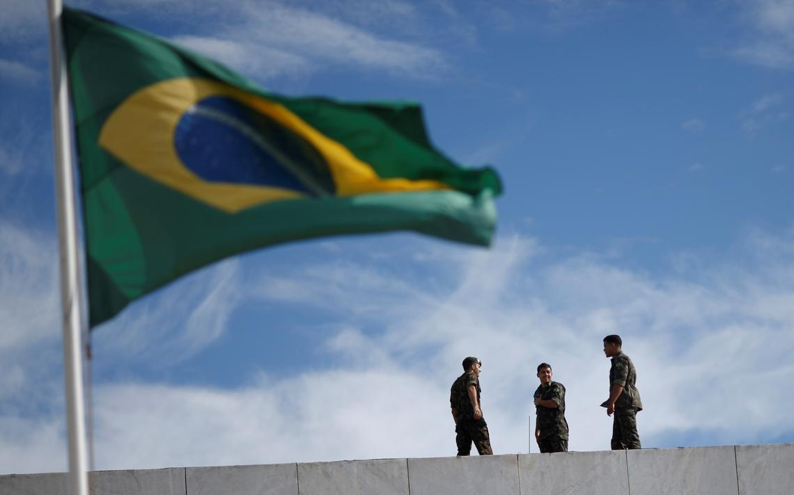 Três soldados fardados em cima do telhado de prédio. À frente deles, uma bandeira do Brasil hasteada e tremulando.