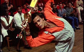 Dançarino de ballroom se dobra para frente enquanto segura um troféu