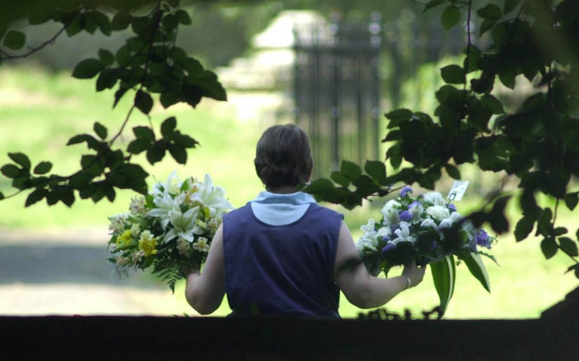 Mulher carrega flores para o funeral de especialista sobre armas do governo britânico David Kelly, que se suicidou em 2003, no Reino Unido