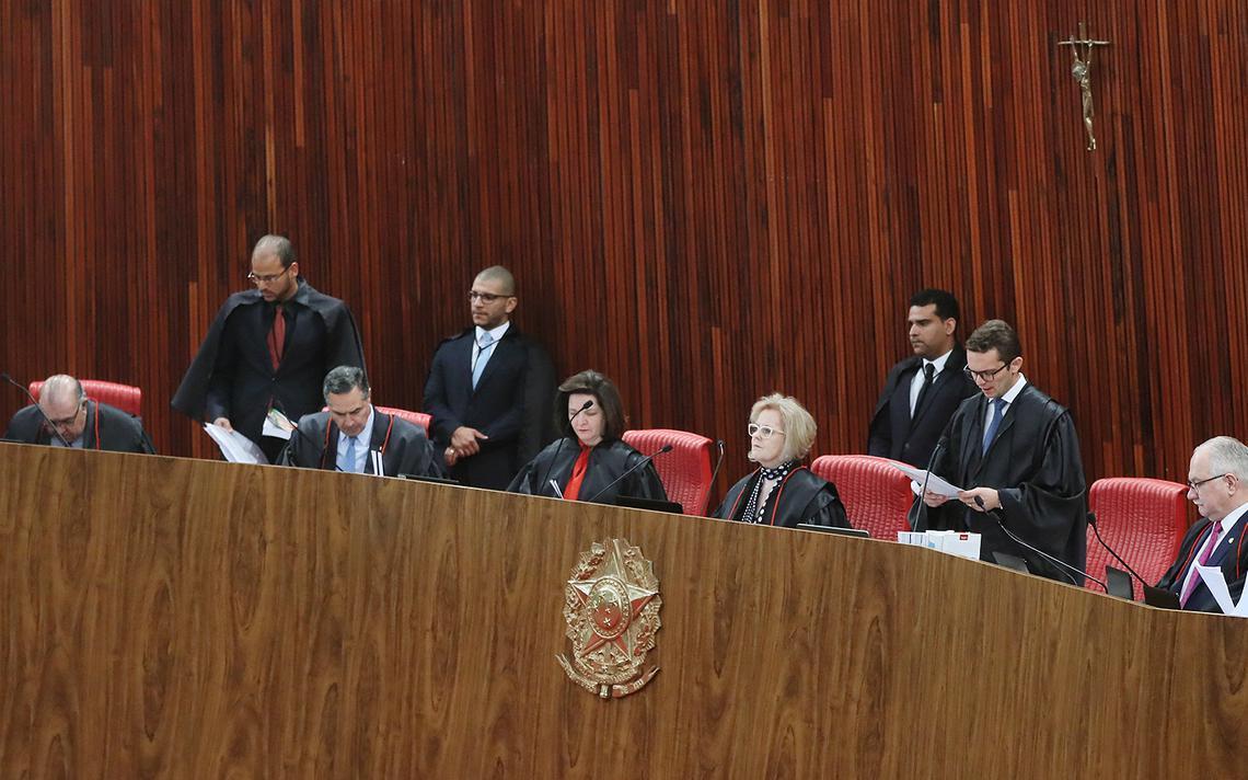 Ministros do TSE e procuradora-geral eleitoral sentados à mesa no plenário do tribunal. Asessores estão em pé. Há um crucifixo colocado na parede atrás da mesa.