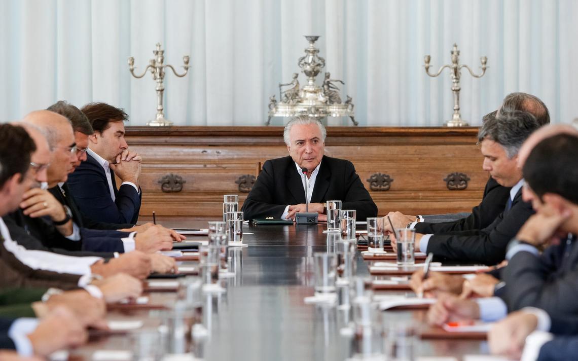 Mesa com os políticos sentados. Na cabeça da mesa e no centro da imagem está Michel Temer.
