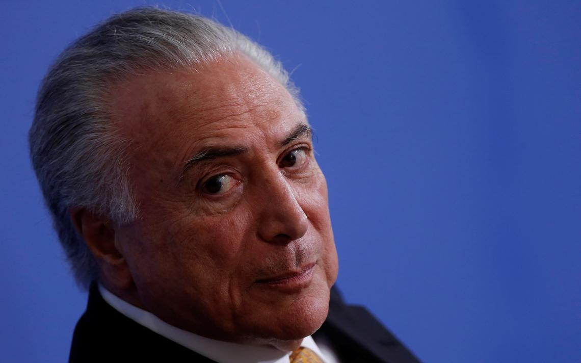 Temer sentado em evento no Palácio do Planalto.