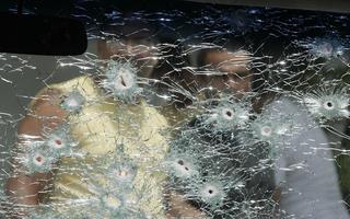 Vidro de carro furado por balas, com pessoas observando