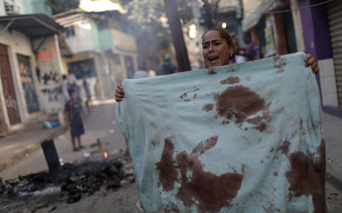 Mulher protesta segurando toalha manchada de sangue de idosa e sua filha, que morreram após embate entre policiais e suspeitos de crimes no Rio, em 2017