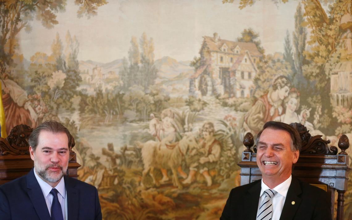 Sentados lado a lado, Toffoli e Bolsonaro têm semblante risonho. Eles estão sentados em cadeiras de modelo antigo, trabalhadas em madeira e que estampam o brasão da República. Atrás deles, um painel com uma pintura de paisagem campestre.