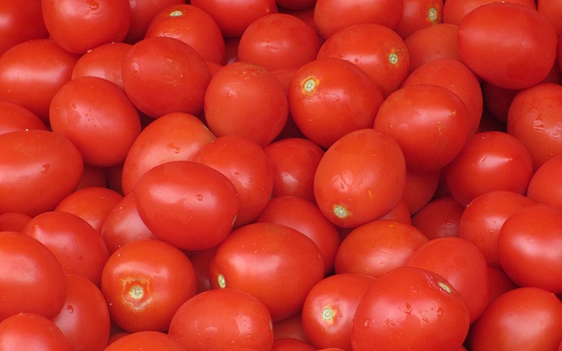 Amontoado de tomates-cereja, bastante vermelhos e um pouco molhados.