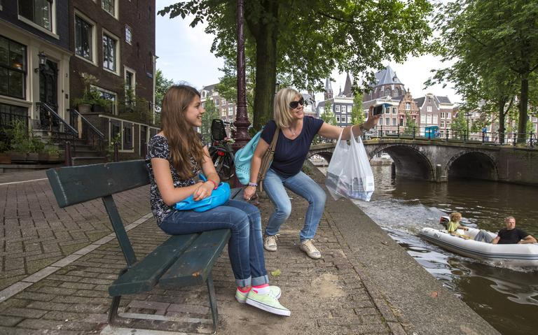 Turistas italianas tiram fotos próximas a canal em Amsterdã, em 2014