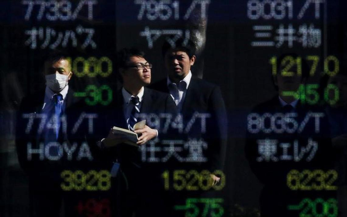 Trabalhadores refletidos em uma tela com índices de mercado em Tóquio