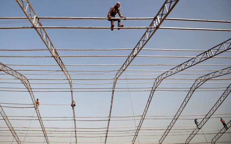 Trabalhadores montam em estrutura para erguer tenda