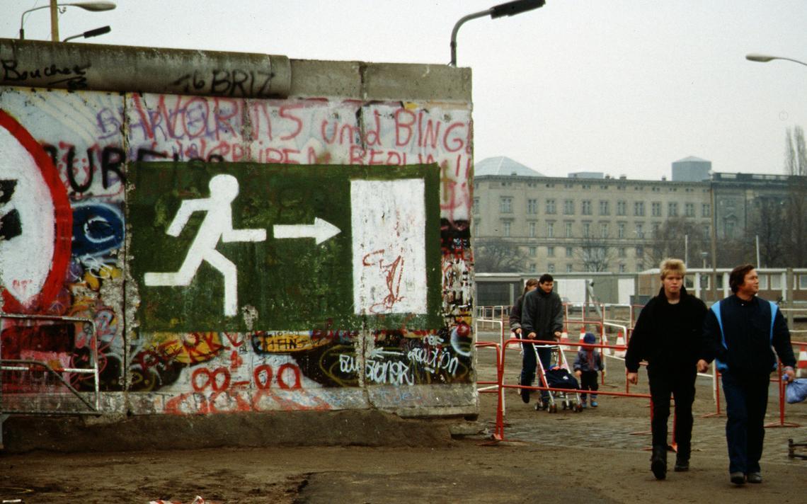 Pessoas andando ao lado de trecho remanescente do muro de Berlim