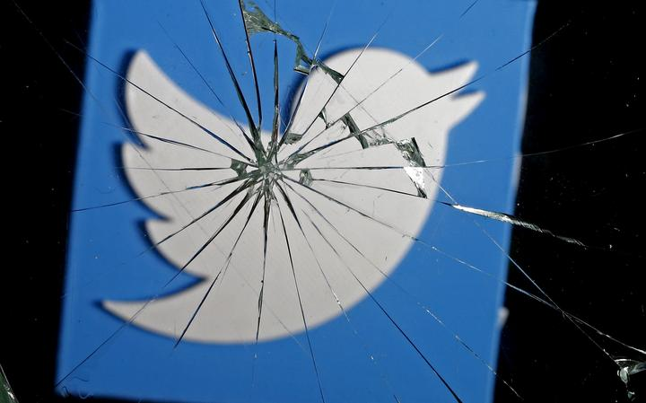 Logotipo do Twitter visto através de um vidro quebrado.