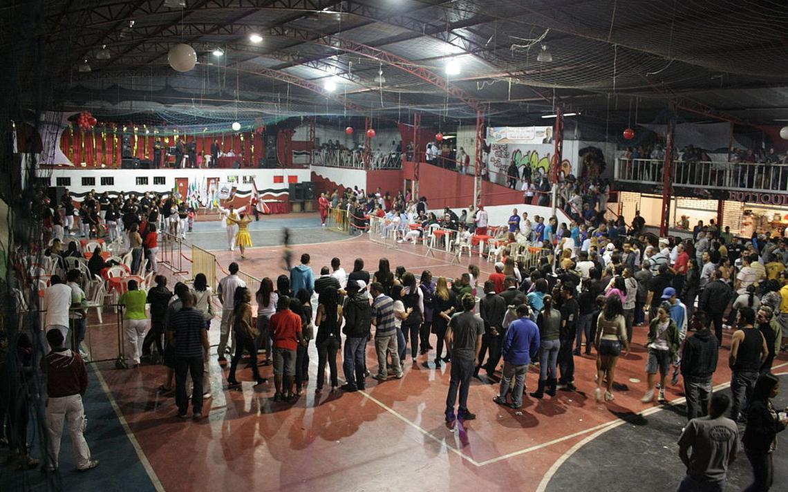 Quadra da escola paulistana Unidos de São Lucas, durante ensaio de mestre-sala e porta-bandeira, com público assistindo.