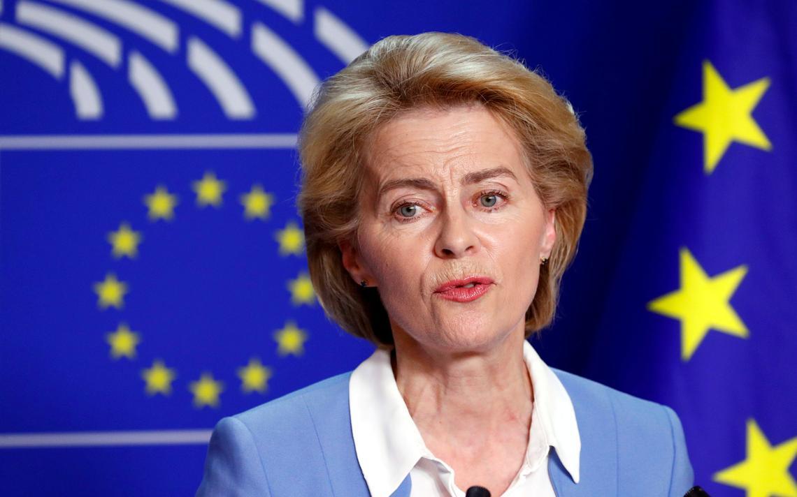 Em pé, von der Leyen fala com dois microfones à sua frente. Atrás, bandeira da União Europeia, com as características estrelas que representam os países-membros.