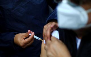 Imagem mostra profissional de saúde aplicando vacina em braço de uma pessoa com máscara
