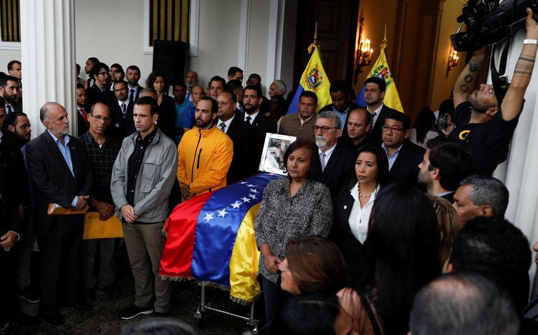 Autoridades em pé, ao lado de caixão. Em cima do caixão, bandeira da Venezuela e um porta-retrato com uma foto de Albán com uma imagem de Jesus Cristo.