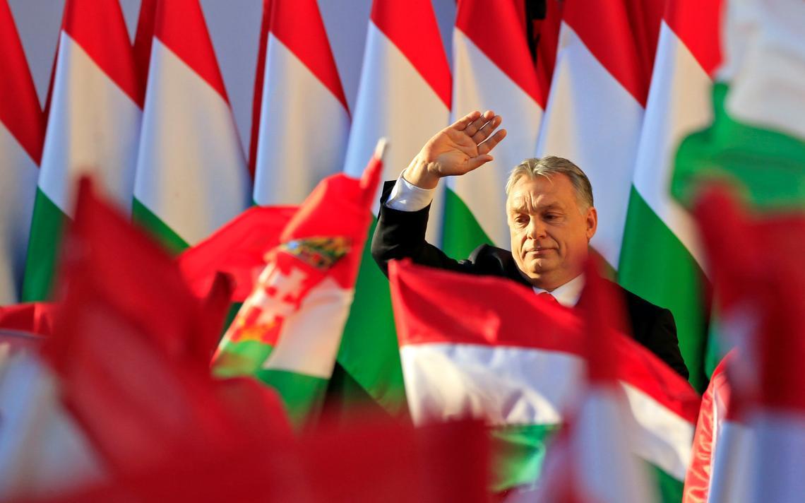 Orbán acena em palanque, com bandeiras atrás e à sua frente.