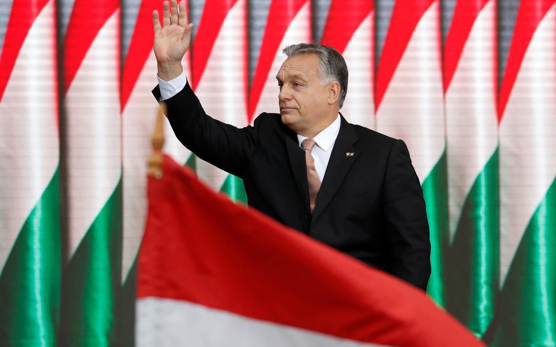 Orbán acena com a mão direita para o público. Atrás dele, várias bandeiras húngaras lado a lado. Na frente, uma bandeira húngara erguida da plateia.