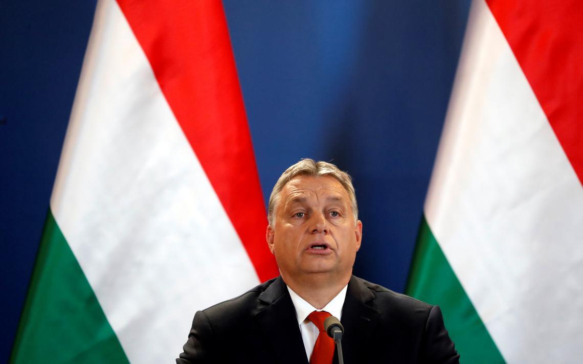 Orbán fala ao microfone. Atrás, duas bandeiras da Hungria.