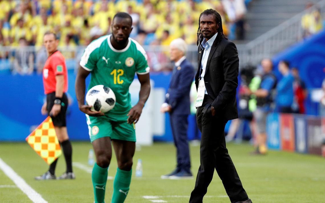 Youssouf Sabaily, de Senegal, se prepara para cobrança de lateral enquanto é assistido pelo técnico Aliou Cissé