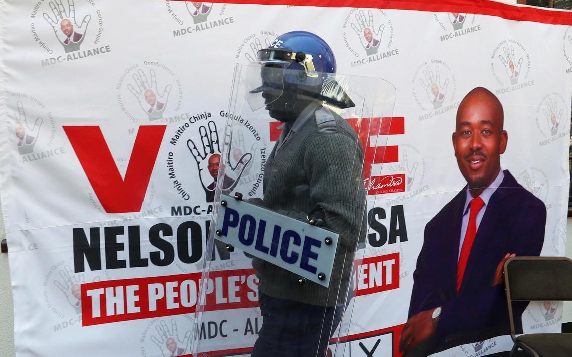 Policial, com capacete e escudo, ao lado de painel de propaganda eleitoral de Chamisa.