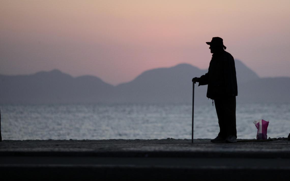 Senhor de idade com bengala no nascer do sol