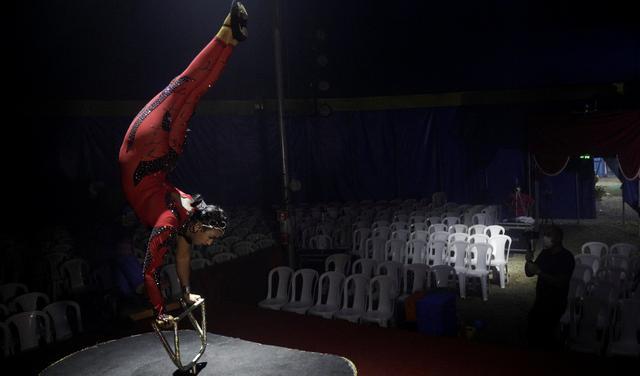 Mulher realiza acrobacia em palco diante de cadeiras vazias enquanto é filmada por um homem de máscara