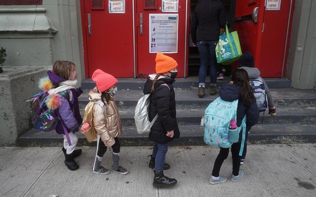 Crianças de lado com máscaras e cheias de casaco esperam sua vez de entrar por portão vermelho, atrás delas