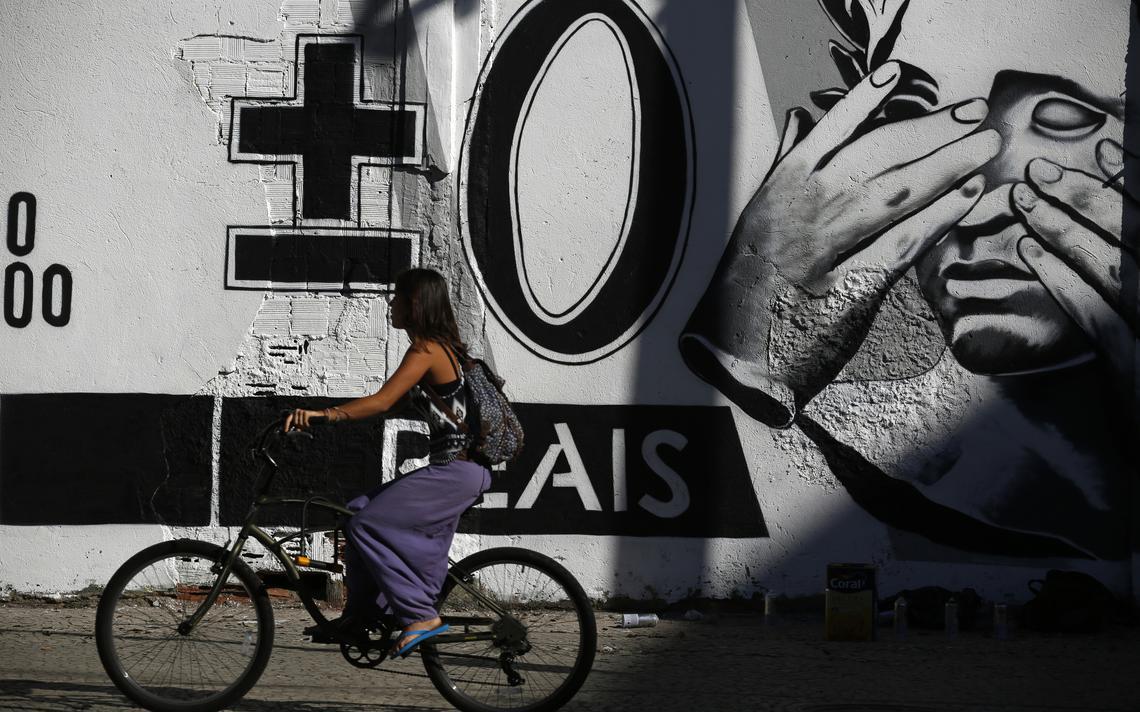 Mulher pedala em frente a grafiti sobre Real, no Rio