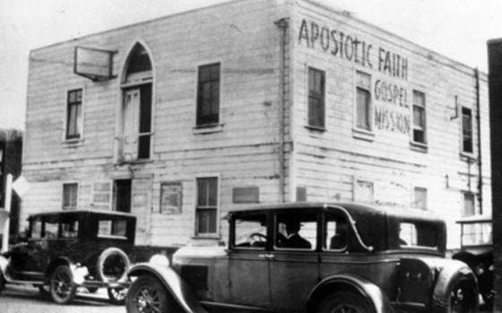 Foto em preto e branco que mostra uma igreja - um prédio branco e quadrado de madeira - com carros antigos na frente