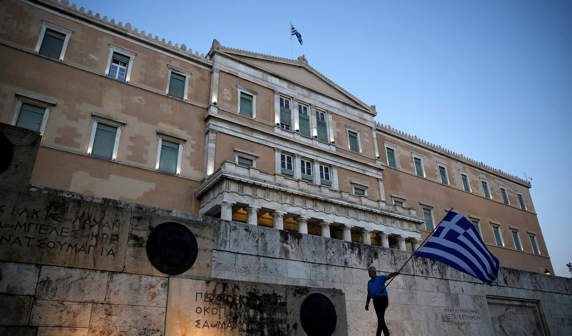 Homem protesta em frente ao prédio do parlamento grego