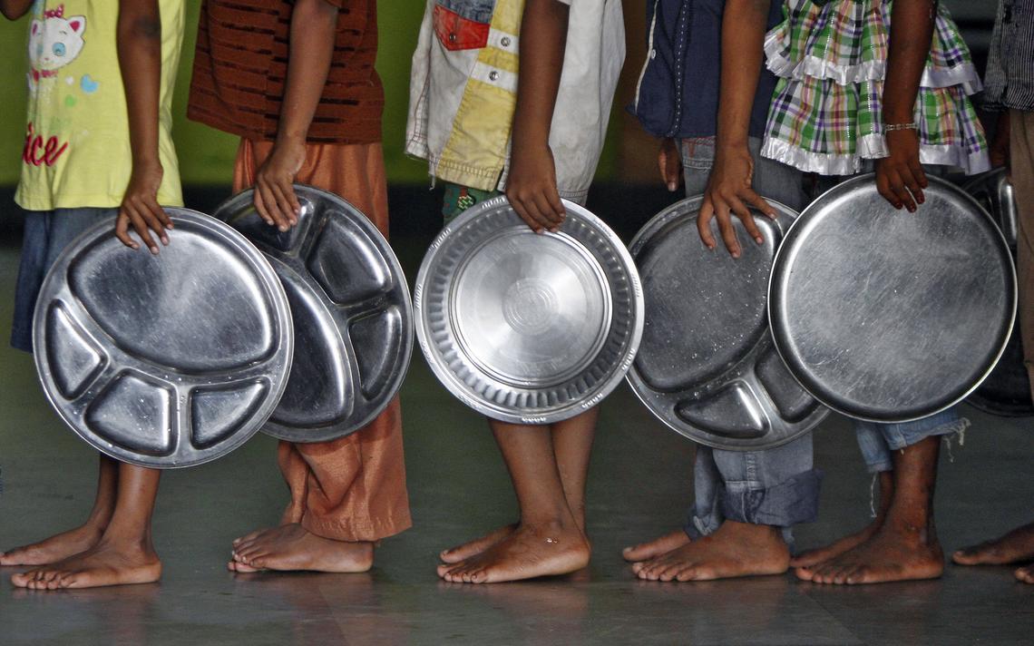 Crianças que vivem em orfanato tocado por ONG na Índia à espera de alimentos