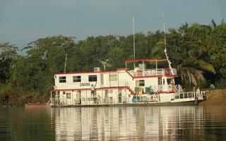 Embarcação com o nome 'Carcará' escrito no convés no leito de um rio com árvores ao fundo