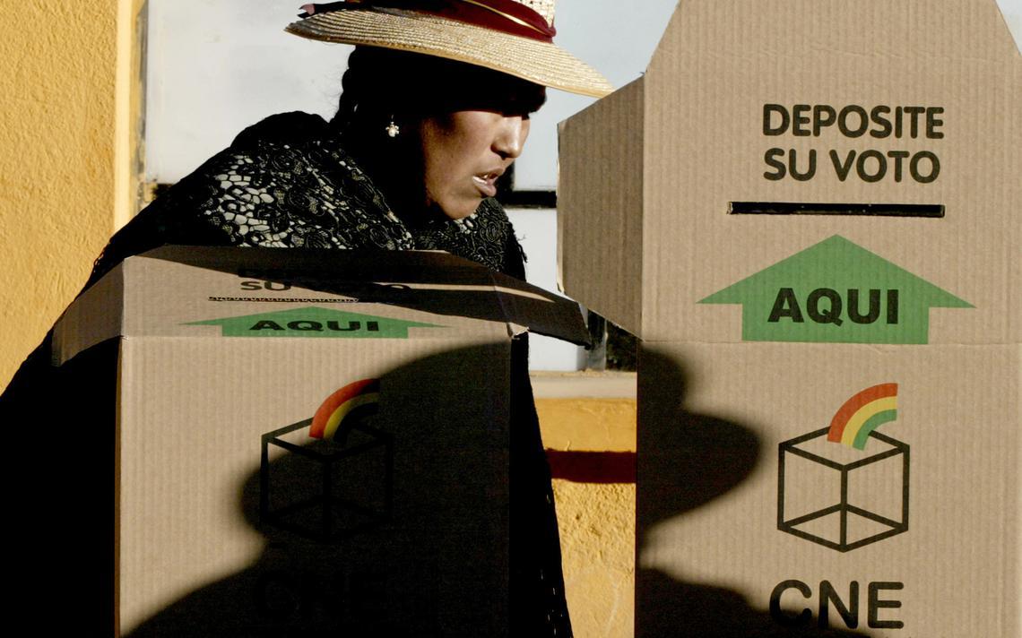 Boliviana ao lado de urna eleitoral na cidade de El Alto