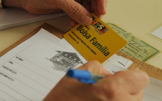 imagem aproximada de mão a preencher ficha relativa ao programa bolsa família. a pessoa também segura, na outra mão, a carteirinha de onde copia os dados.