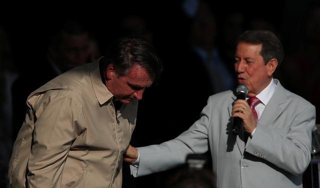 Jair Bolsonaro, de casaco, se inclina para frente enquanto o pastor R.R. Soares, de terno, segura seu braço com uma mão e um microfone com a outra.