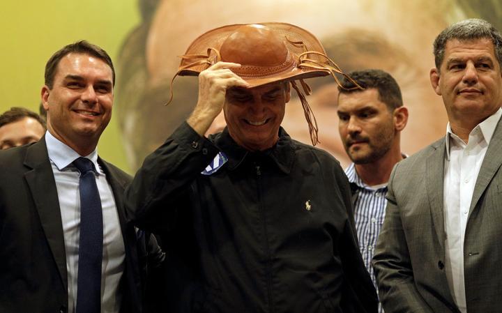 Bolsonaro veste chapéu nordestino, ao lado do filho Flavio (esquerda) e do presidente do PSL, Gustavo Bebianno