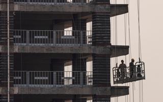 Dois homens estão em andaime próximos a prédio em construção