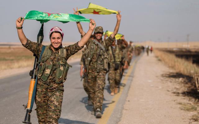 Forças curdas carregam bandeiras em Tel Abyad