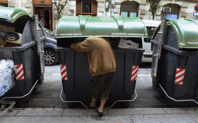 Homem procura comida em lixo na rua