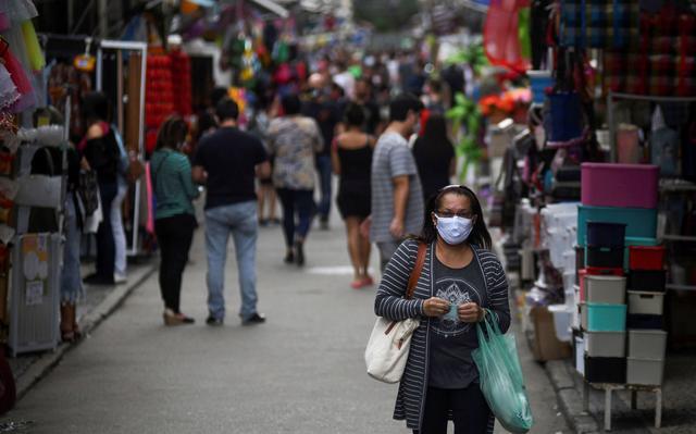 Uma mulher segura uma sacola de compras e usa uma máscara enquanto passa em frente a lojas de ruas. Ao fundo, é possível ver outras pessoas olhando os produtos e fazendo compras, com alguma aglomeração.