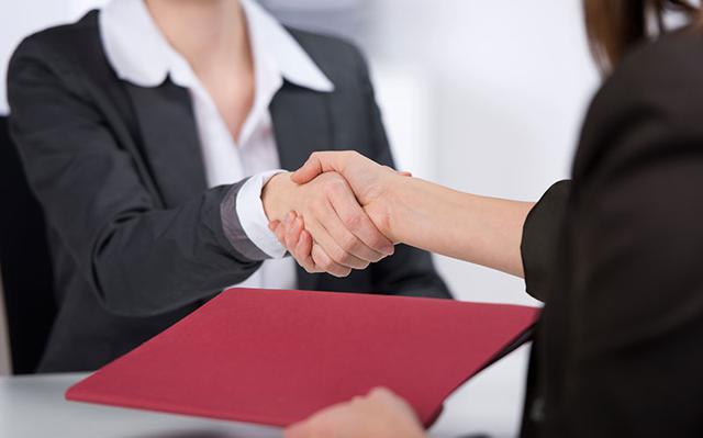 duas pessoas vestidas profissionalmente apertam as mãos. uma delas segura uma pasta vermelha