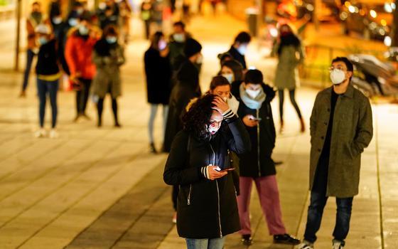 Foto mostra grupo de pessoas esperando em fila numa praça em Madri para serem testados para a covid-19; algumas pessoas olham para a tela do celular