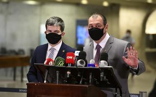 Imagem mostra Randolfe Rodrigues e Omar Aziz, ambos de terno e máscara preta, atrás de um púlpito com vários microfones de redes de televisão, dando entrevista. Aziz está com o braço esquerdo erguido, mostrando a palma da mão, em sinal para alguém esperar