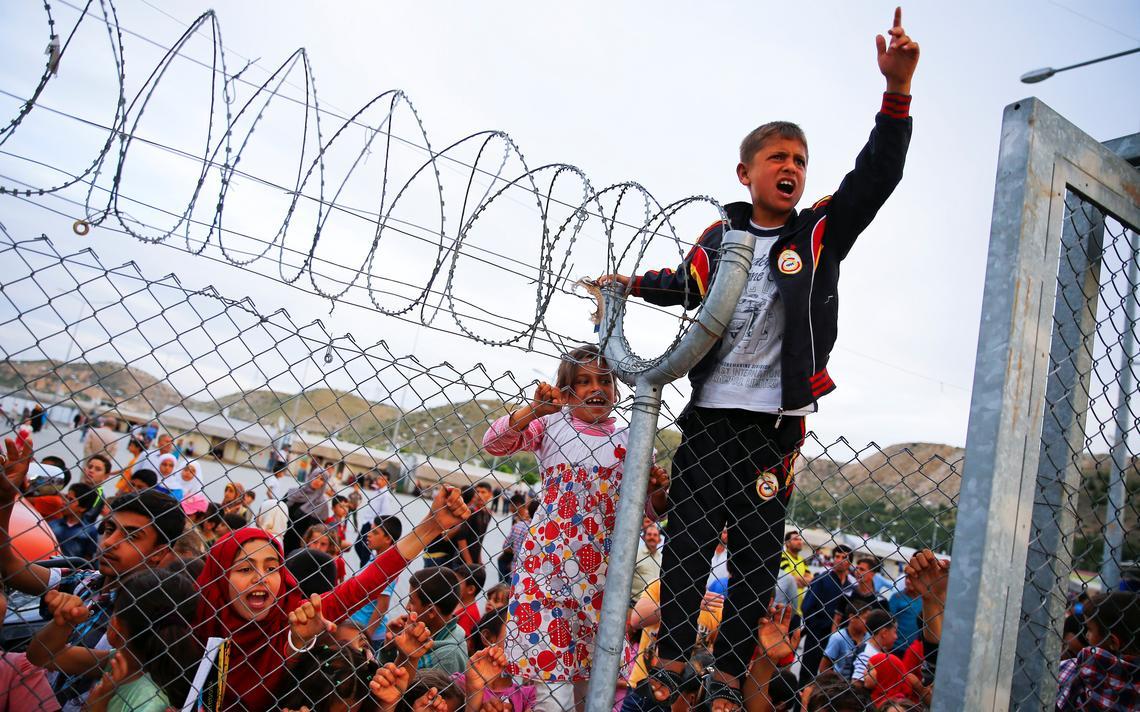 Garoto refugiado esticula ao lado de arame farpado
