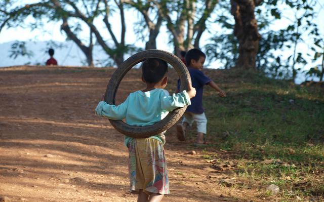 Um menino, visto de costas, segura um pneu no corpo, como se fosse um bambolê. Outro menino, mais longe, aponta para a grama.