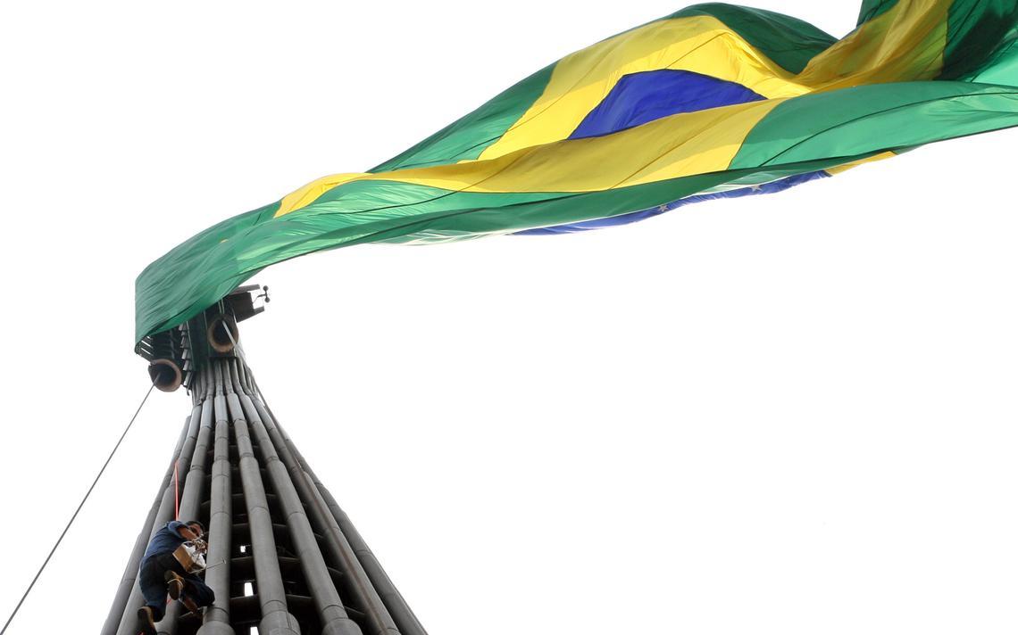Homem sobe no mastro da bandeira do Brasil na Praça dos Três Poderes