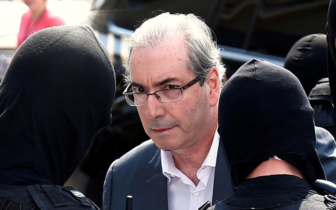 Cunha é escoltado por policiais após ser preso, em outubro de 2016