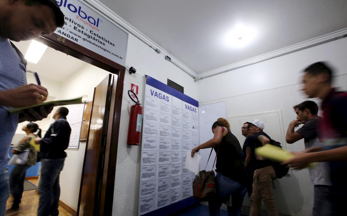 Pessoas observam relação de vagas em uma agência de emprego em São Paulo