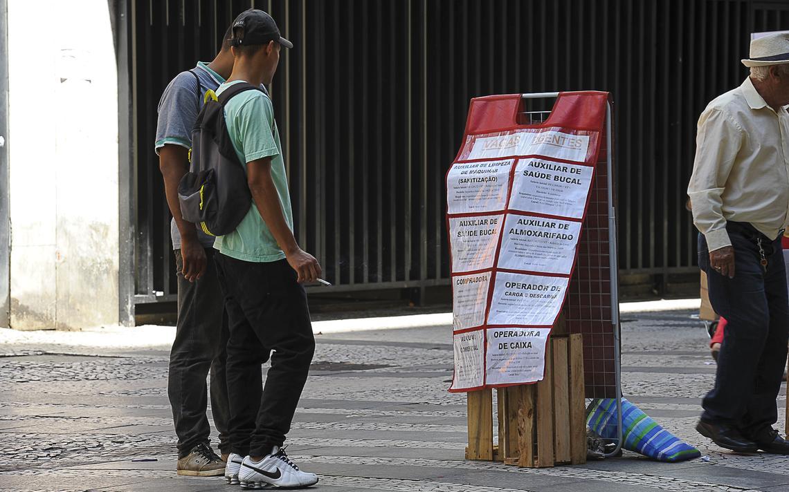 Homens leem anúncios de vagas no centro de São Paulo